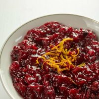 Make easy Low Carb Oven Cranberry Sauce with fresh cranberries and orange zest for your next holiday gathering. Ready in under 30 minutes!
