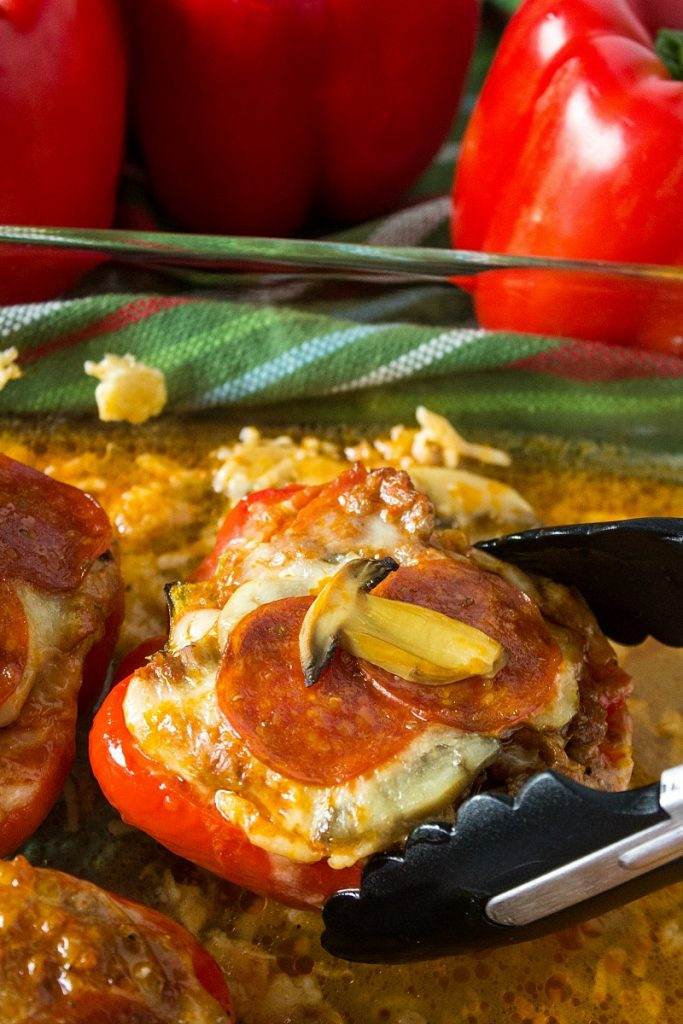 Low Carb Pizza Stuffed Peppers - Sausage, pepperoni, mushrooms and cheese, smothered in pizza sauce and baked inside a red bell pepper.